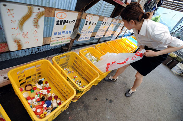 A resident divides up her bottles into clear, brown and other coloured bottles at the waste disposal site in central Kamikatsu Town in Shikoku, Japan on July 22, 2008. There are no rubbish collection services to the 800 households in the town and residents are required to carry all their non-compostible rubbish to one waste disposal site and divide it up into 34 different types for recycling. Commissioned: recycling, zero waste story Photographer: Robert Gilhooly